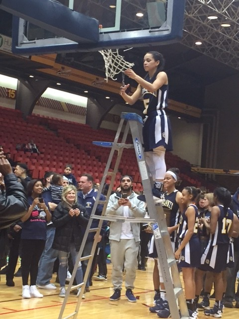 Sophomore Mariah Modkins cuts down the net following her game winning free throws for the Lady Comets.