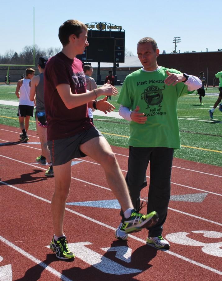 Coach Sabol talks to junior runner Joe Riordan about his workout.