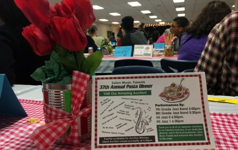 "The theme of this year's Pasta Dinner was Italy, and the Music Parents decorated the cafeteria in accordance with it. Tables were adorned with centerpieces of flowers and spaghetti noodles in tomato cans, lights and black curtains were hung behind the makeshift ""stage,"" and bowtie noodles were scattered across the checkered tablecloths."