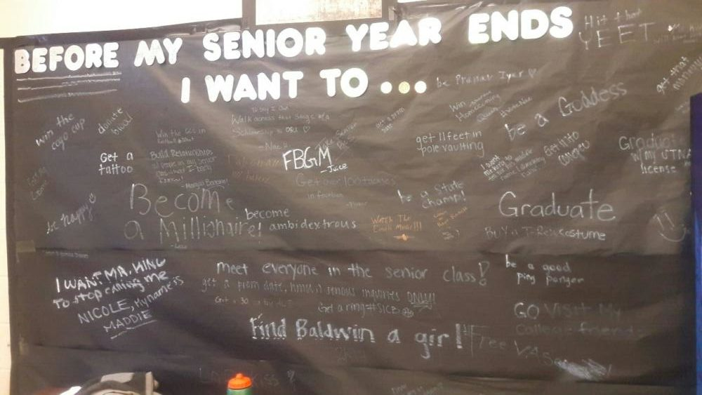 Seniors write what they wish to accomplish during their last year on a poster in Senior Commons.