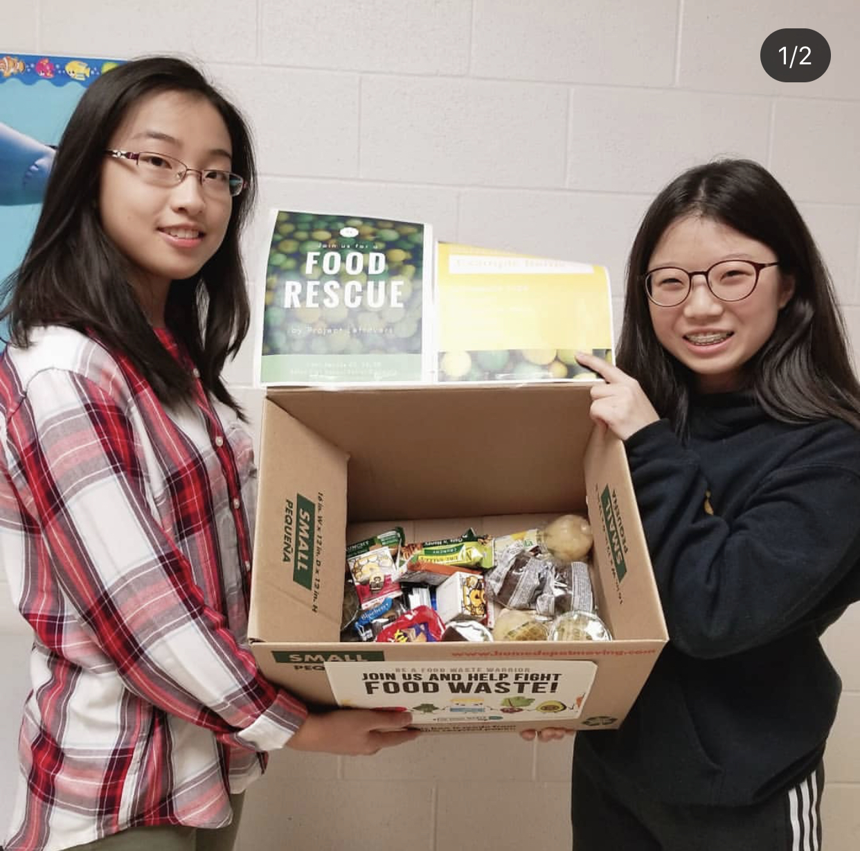 Katherine Dai (left) and Lea Kim (right) standing with a box of collected food items. PC: @projectleftovers on IG