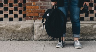 A teen girl stands outside with her backpack. Photo courtesy of unsplash.com