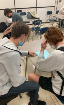Peer leader Jordan Blaugrund helps a student on a math problem in Ms. Moeschbergers classroom.